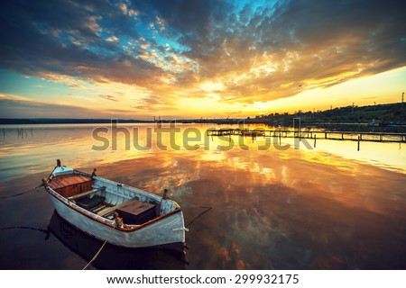 Boat on lake with a reflection in the water at sunset - stock photo