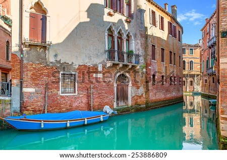 Boat on narrow canal among old brick houses in Venice, Italy. - stock photo