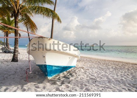 boat on sandy Tropical Caribbean beach - stock photo