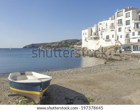 Boat on the beach and white houses near the coast, coastal landscape - stock photo
