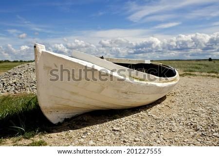 Boat on the beach at sunrise time, Estonia, Saaremaa, Baltic Sea - stock photo