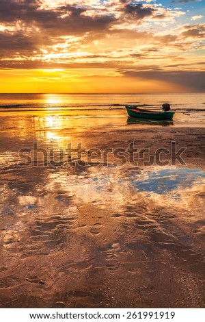 Boat on the beach at sunset in tide time. - stock photo
