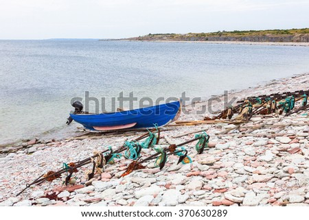 Boat on the beach with fishing tools - stock photo