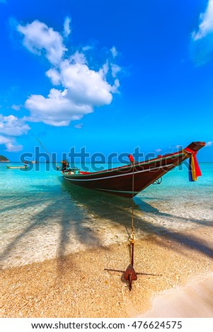 Boat on the beach with palm trees and shade from trees