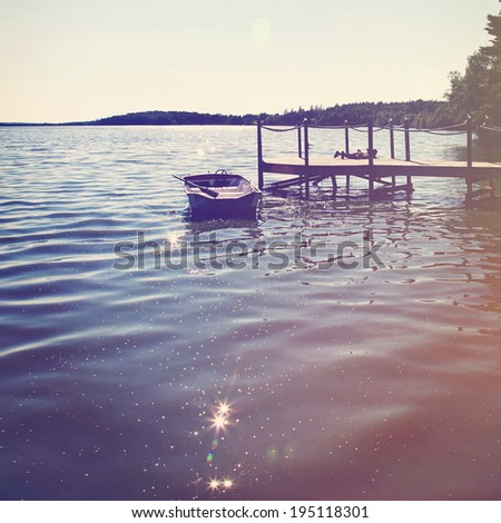 Boat on the lake by the dock in summer - stock photo