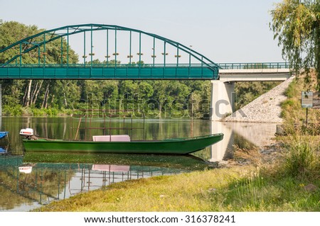 BOAT ON THE RIVER WITH BRIDGE IN THE BACKGROUND. - stock photo