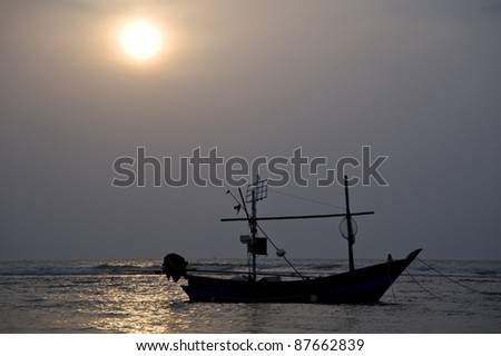 boat on the sea and sun set - stock photo