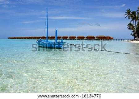 boat on tropical beach in front of holiday villas