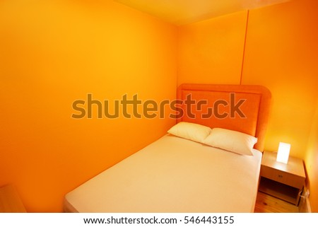 boat or cruise ship cabin bedroom with small night table and orange double bed