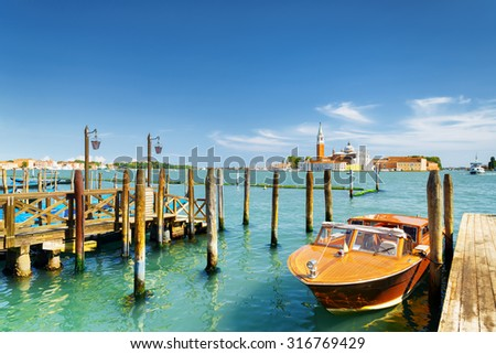 Boat parked at pier beside the Riva degli Schiavoni on the Venetian Lagoon in Venice, Italy. The Church of San Giorgio Maggiore on island of the same name is visible in background. - stock photo