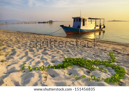 Boat parked on the beach at Sunset - stock photo