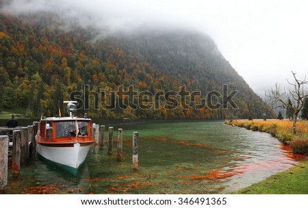 Boat parking on Lake Konigssee with wooden pier and fallen leaves by lakeside on a misty foggy morning ~ Beautiful autumn scenery of Koenigssee (King's lake) in Bavaria, Germany - stock photo