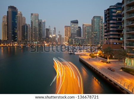 Boat Passing between skyscrapers of Dubai Marina in the Dusk. Dubai Marina is an artificial canal city, carved along a two mile stretch of Persian Gulf shoreline. - stock photo