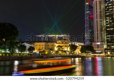 BOAT QUAY, SINGAPORE - JULY 29, 2016: A tourist boat passes the historic Boat Quay area as a laser light show display from Marina Bays Sands resort shows in the background