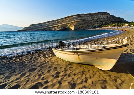 Boat resting on the sands of Matala beach at sunset, island of Crete, Greece - stock photo