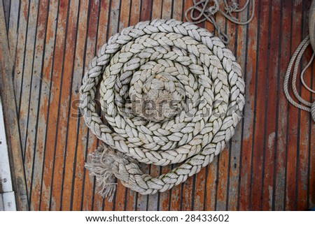 Boat rope in tidy spiral coil on desk - stock photo