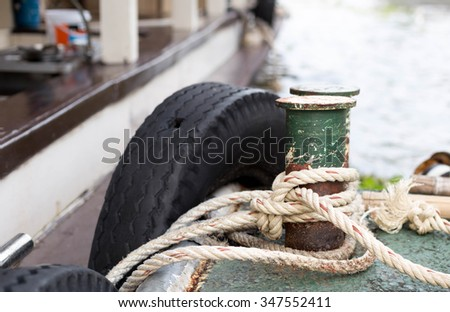 Boat rope tied to the old iron cleats on deck - stock photo