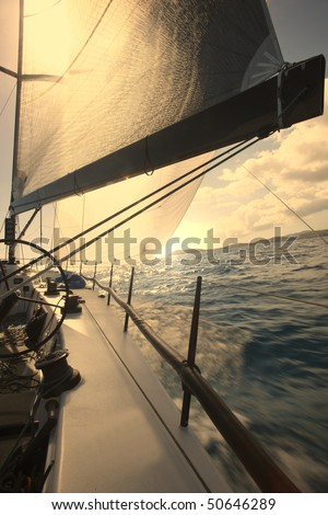 Boat sailing in the ocean during sunset. - stock photo