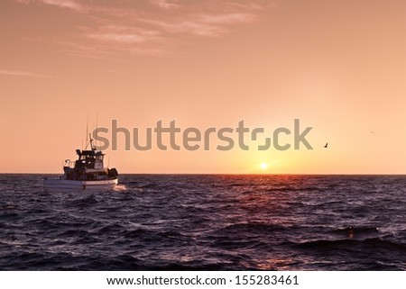 Boat sailing towards the sunset on the Pacific ocean - stock photo