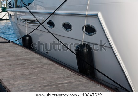 Boat secured to a wooden dock or pier.  Shows side of boat and rubber fenders along side the dock. - stock photo