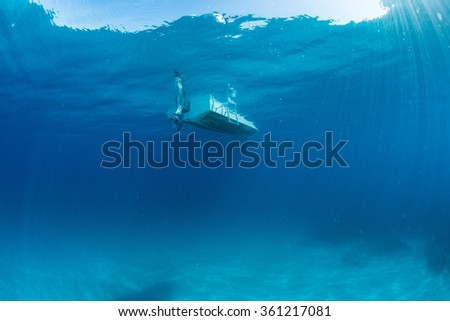 boat ship from underwater turquoise paradise waters - stock photo
