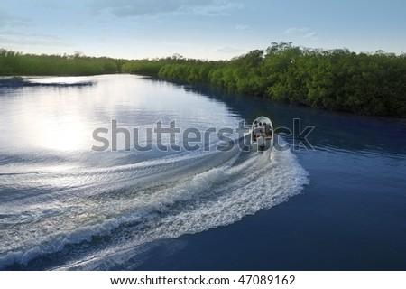 Boat ship wake prop wash curve on sunset lake river - stock photo