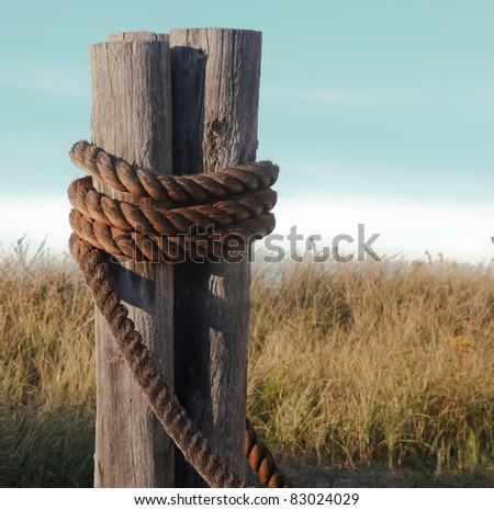 Boat/Ships rope anchored on post.  Image taken in Wisconsin on the banks of Lake Superior.  Focus is on the foreground. - stock photo