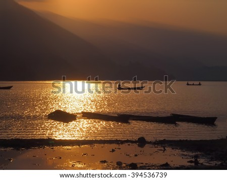 Boat  silhouette during sunset -art of  ray light at Phewa lake in Nepal - stock photo