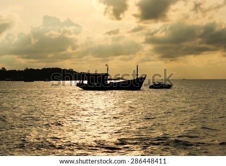 Boat silhouette in the sea against sunrise  - stock photo