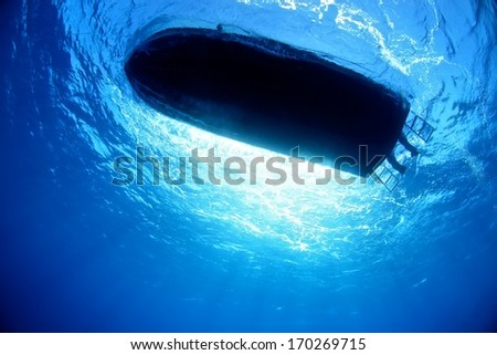 Boat silhouette under water with beautiful sun ray. - stock photo