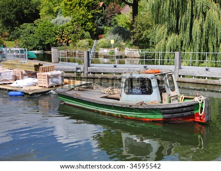 Boat towing a Pontoon of building supplies along the River Thames in England