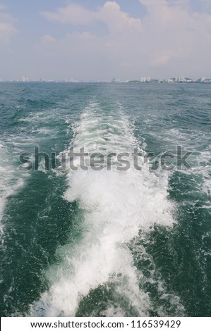 Boat wake on the water behind the boat in the sea - stock photo