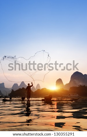 Boat with cormorants birds, traditional fishing in China use trained cormorants to fish, Yangshuo, China - stock photo