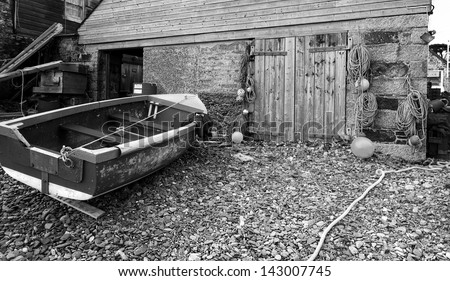 Boat with fisherman's jacket on near boat shed on shingle beach - black and white.
