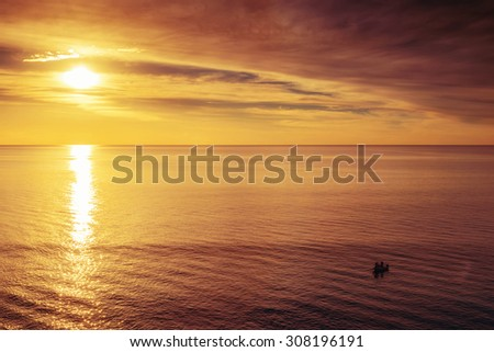 Boat with fishermen at sunset. Red color toning applied - stock photo