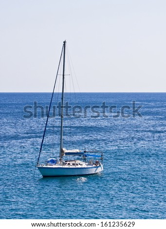 Boat with mast at sea with a gray sky - stock photo