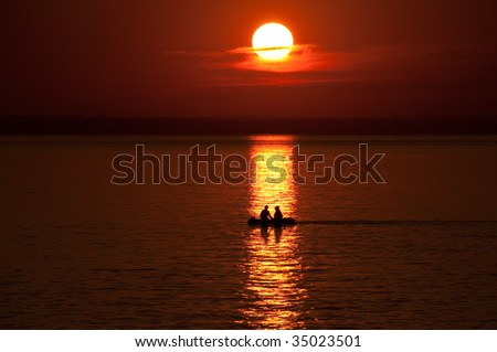Boat with 2 people against an orange sunset - stock photo