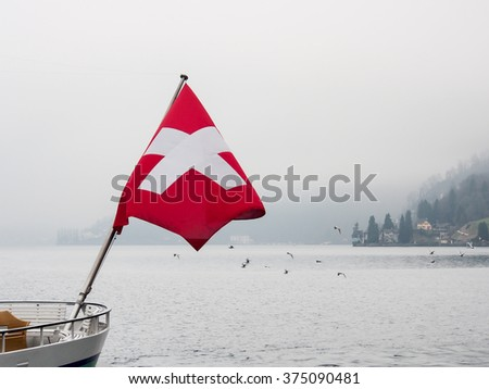 boat with Swiss flag in the lake of Luzern - stock photo