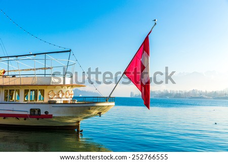 Boat with Swiss Flag on Lucerne, Switzerland. - stock photo