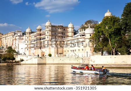 Boat with tourist on the Pichola lake with City Palace view at blue sky in Udaipur, Rajasthan, India - stock photo