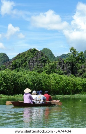 Boat with tourists on river in mountain landscape - stock photo