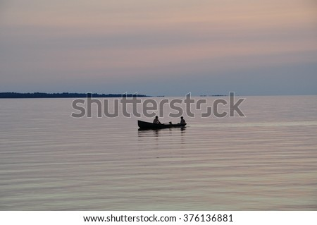 Boat with two men in the middle of the lake - stock photo