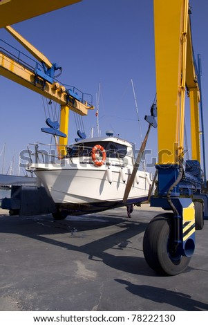 boat yellow crane travelift lifting motorboat for yearly antifouling hull treatment - stock photo