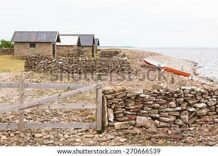 Boathouse by the beach with boats drawn up - stock photo