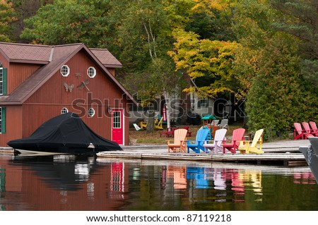 Boathouse with a boat and colorful chairs - stock photo