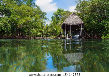 Boathouse with palm roof and lush tropical vegetation reflected on water surface, Bocas del Toro, Caribbean sea, Central America, Panama - stock photo