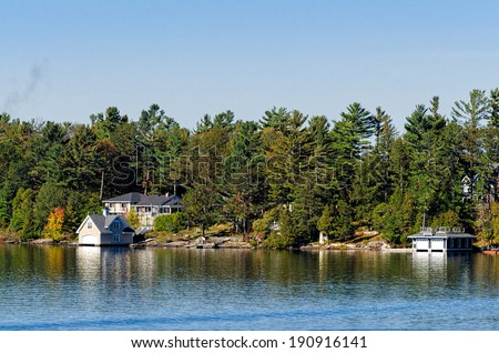 Boathouses and cottages on a lake - stock photo