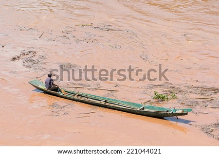 boatmen paddle their boats on the shore of the Mekong River in During the flood at Luang Prabang, Laos - stock photo