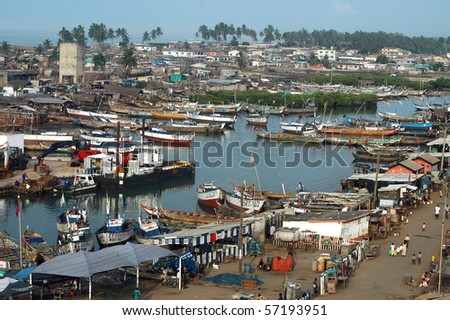 Boats an houses at Elmina harbour in Ghana - stock photo