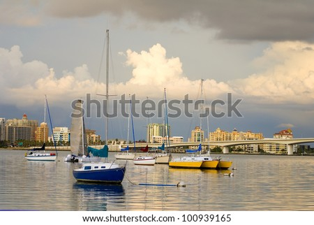 Boats anchored in a harbor under cloudy skies - stock photo